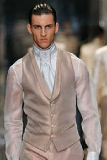 A custom tailored v-neck four button men's vest with a medium gorge, a shawl collar, a satin back, piped lower pockets, and a narrow v bottom.