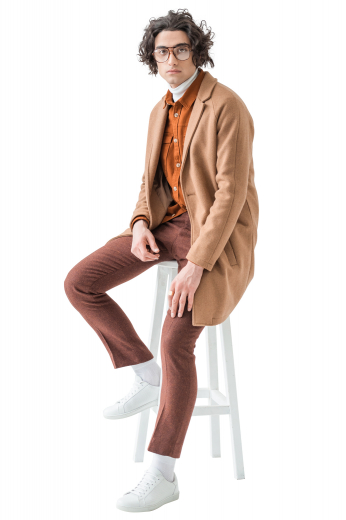 This men's custom made tan colored coat is tailor made in a fine wool and tweed, featuring a single breasted button closure, slanted welt pockets, and a center vent.