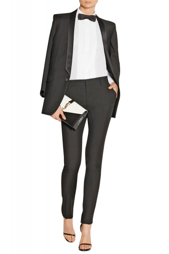 Game up your style quotient with this womens bespoke cashmere wool black tux, featuring a womens handmade slim fit tuxedo jacket and womens tailor made tuxedo pants. The womens custom made tuxedo jacket features a stunning single breasted pattern with 1 front close button, an elegant shawl collar with satin facing lapels, and 2 lower flapped pockets. The womens tailor made suit pants with flat fronts have a classic slim cut fitting with extended belt loops, a zipper fly, 2 front slash pockets, and 2 back pockets.
